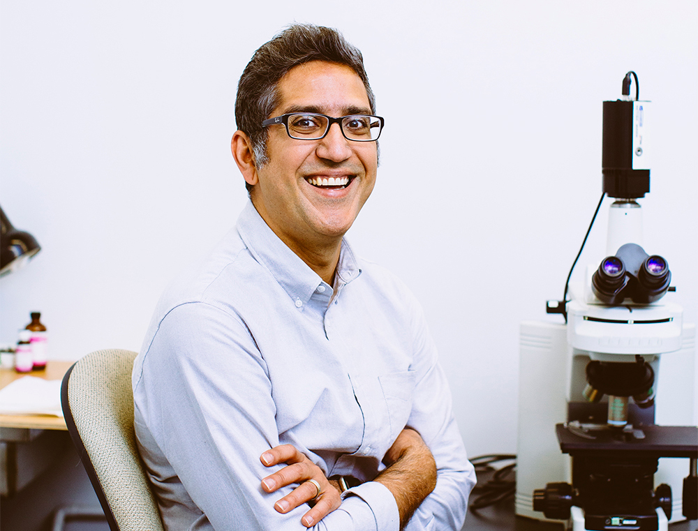 Arash Komeili next to a microscope