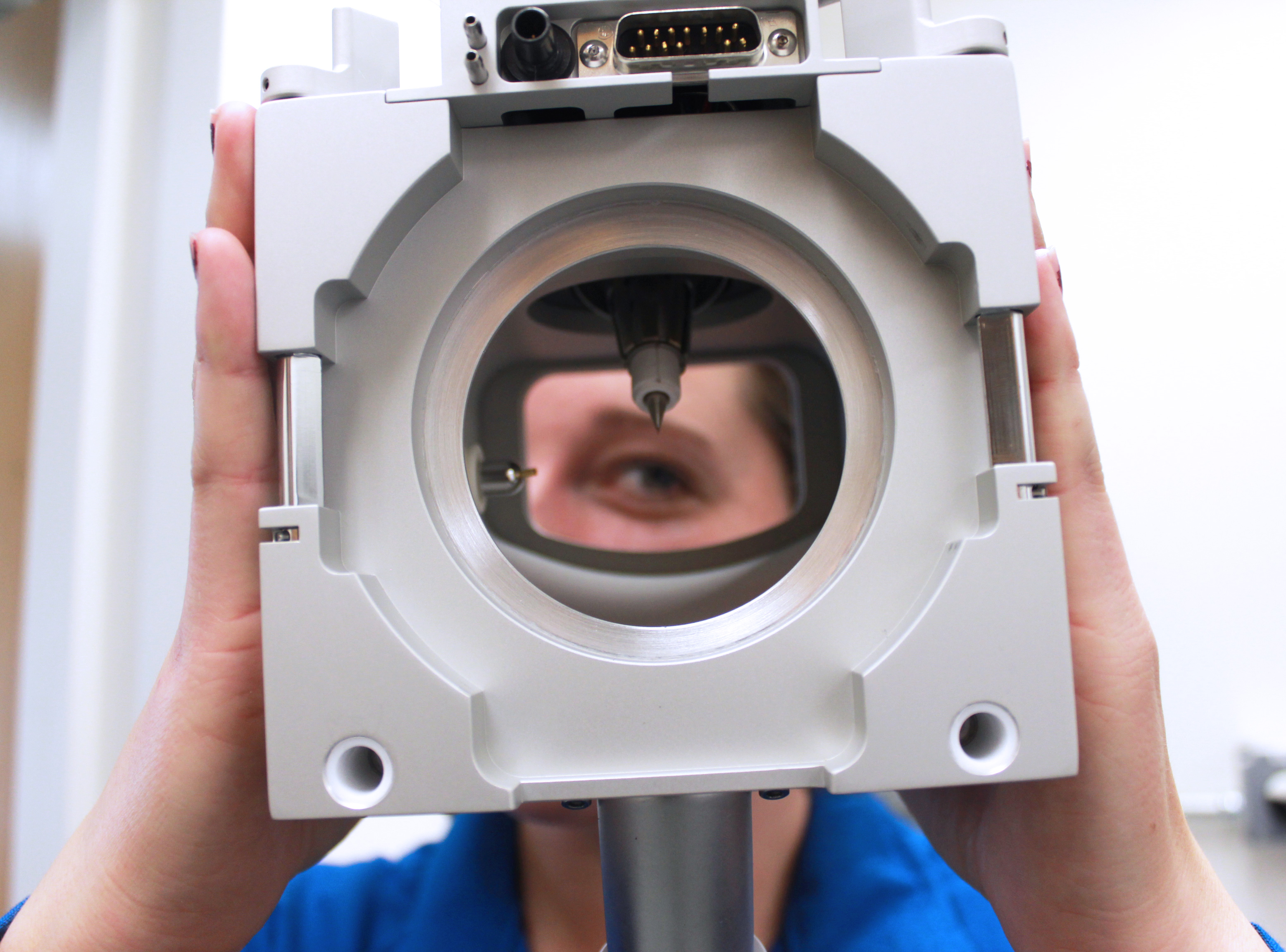 A researcher looking through a piece of equipment