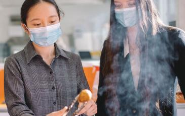 Siwen Liu (left) holding a plant-based meatball wit tongs.
